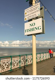 "PENARTH, VALE OF GLAMORGAN - AUGUST 2018:  ""No fishing"" sign on the pier in Penarth, Wales. In the background are decorative painted railings."