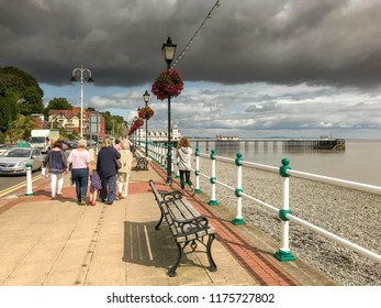 PENARTH, VALE OF GLAMORGAN - AUGUST 2018: People walking on the promenade in bright sunshine in Penarth, Wales. A large dark cloud is in the sky.