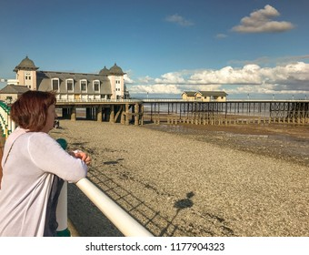 PENARTH, VALE OF GLAMORGAN - AUGUST 2018: Person leaning on railings on the esplanade in Penarth, Wales. In the background is the Victorian-era pavilion and pier.