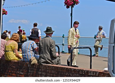Penarth, Vale of Glamorgan / Wales UK - 7/19/2018 : Lunch-break during filming of 'Six minutes to Midnight'. Penarth Pier, S.Wales. Handsome man in hat leans casually against railings on promenade.