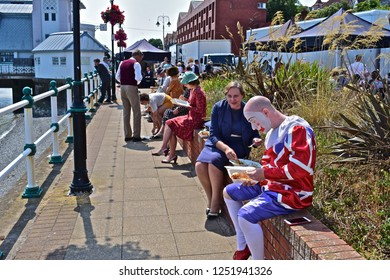 Penarth, Vale of Glamorgan / Wales UK - 7/19/2018 : Actors / Extras enjoying a lunch-break, sitting on a wall overlooking Penarth Pier during filming of the pre-WWII drama 'Six minutes to Midnight'.