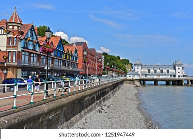 Penarth, Vale of Glamorgan / Wales UK - 7/19/2018 : People enjoying the sunshine, strolling along the promenade on Penarth seafront with the beautiful Art Deco period pier building n the background.