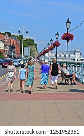 Penarth, Vale of Glamorgan / Wales UK - 7/19/2018 : People enjoying strolling  along  Penarth promenade in the warm summer sunshine, with the classic Art Deco period pier building in the distance.