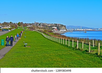 Penarth, Vale of Glamorgan / Wales UK - 1/18/2019: People enjoying fresh and exercise by walking along the cliff top path at Penarth, overlooking Bristol Channel. Art Deco Penarth pier in distance.