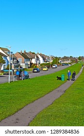 Penarth, Vale of Glamorgan / Wales UK - 1/18/2019: A row of expensive suburban houses with stunning sea views over towards the Bristol Channel and England beyond. Couple walking with pushchair and dog