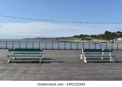 Penarth, Wales- August 8th 2019:British Summer holiday scene. Empty benches on Penarth pier.