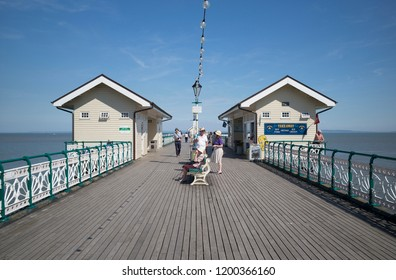 Penarth, Wales / UK - July 7 2018: Deck of Penarth pier, with wooden boards and cast iron railings, and visitors