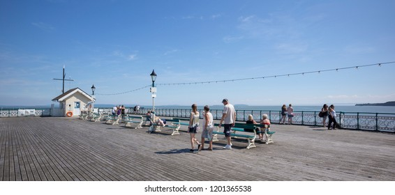 Penarth, Wales / UK - July 7 2018: Visitors at the end of the pier in sunny summer weather