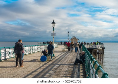 Penarth, Wales, United Kingdom - November 20, 2016: On a cloudy winter day a photo shoot is taking place on Penarth Pier while anglers are fishing and people are enjoying a walk.