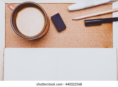 Pen,book,pencil and coffee on cork board background