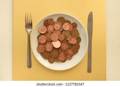 Pence coins on white plate on gold background top view
