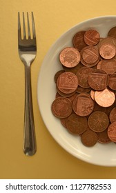 Pence coins on white plate on gold background with fork by the side