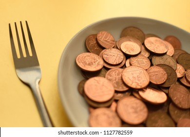 Pence coins on white plate on gold background with fork closeup