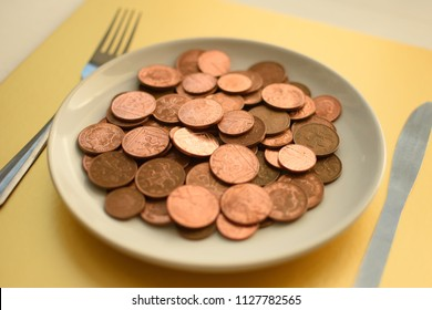 Pence coins on white plate on gold background with cutlery