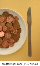 Pence coins on white plate on gold background with knife on side
