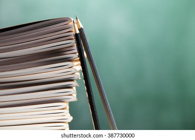 penceils lean on stack of exercise books