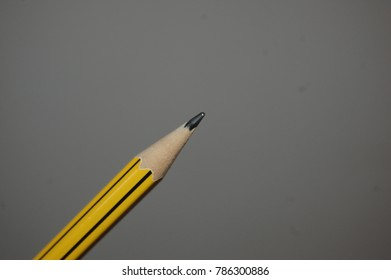 Pencil being held up against plain background. Yellow and Black.