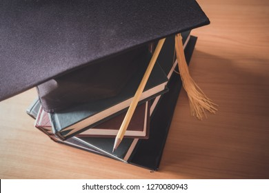 Pencil books and graduation caps, educational concepts