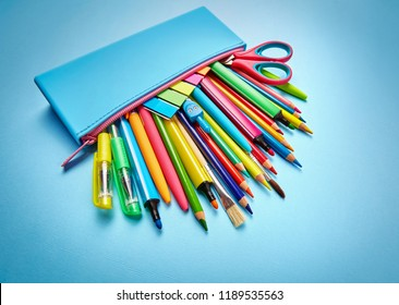 The pencil case is filled with pens, pencils, markers, brushes, scissors and stickers. Educational background. School and office supplies frame