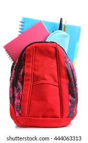pencil case with folders and school supplies in a red backpack on a white isolated background
