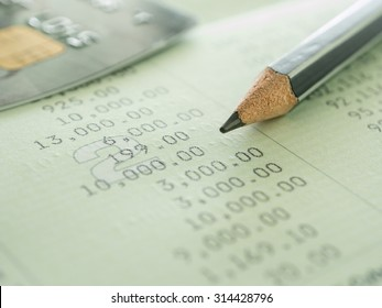 pencil and credit card on bank account. concept of savings, personal loan.