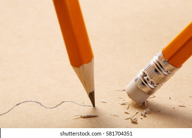 pencil draws a wavy line on paper and pencil rubber eraser removing stripe. Business Breaking concept.