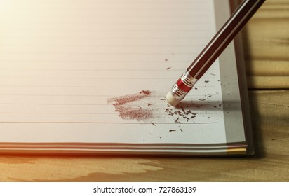 pencil eraser with eraser dust on notebook, remove pencil drawing from notebook in close up view, mistake and error concept