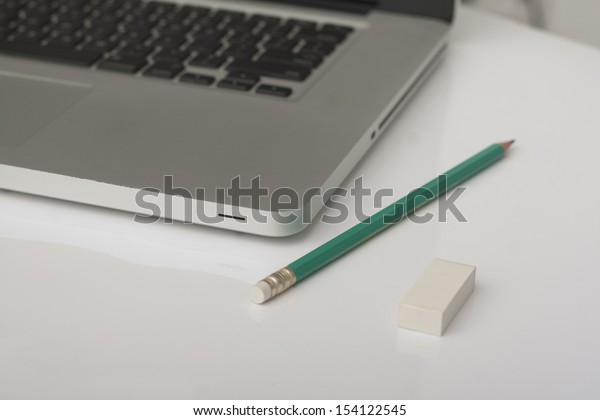 pencil and eraser next to laptop in the office