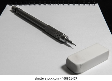 The pencil and eraser on the book.