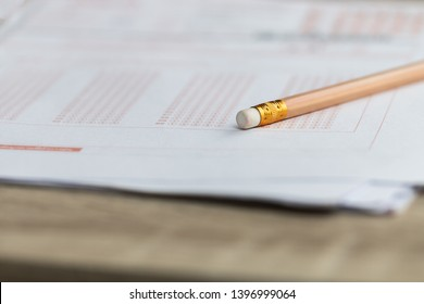 Pencil eraser on standardized test exam multiple carbon paper form with answers bubbled at university classroom. Examination knowledge in school concept