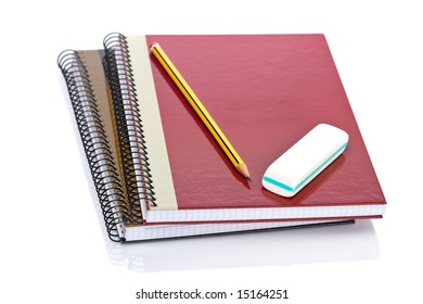 Pencil and eraser on a two notebooks reflected on white background. Shallow depth of field