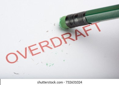Pencil eraser trying to remove the word 'overdraft' on paper, concept of growing debts or credit, financial struggles