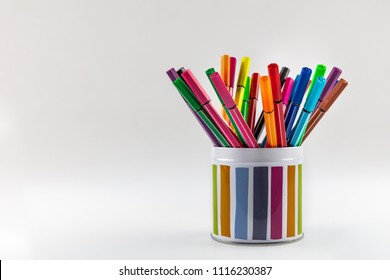 Pencil holder full of colorful pencils isolated over white background