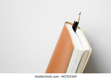 Pencil insert between leather diary on white desk