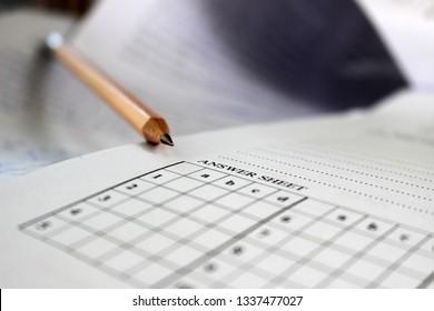 A pencil lies across a blank student answer sheet of an exam paper.