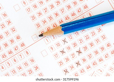 Pencil and lottery ticket with ticked numbers
