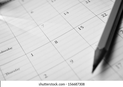 Pencil lying on a calendar showing different dates and days conceptual of schedules, time management, events, deadlines and organisation