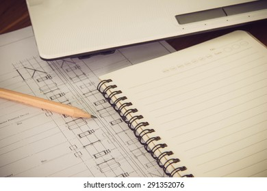 Pencil, notebook with architectural blueprint of office building