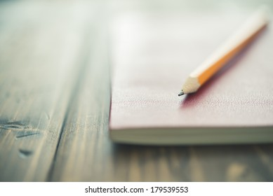 A pencil and a notebook up close