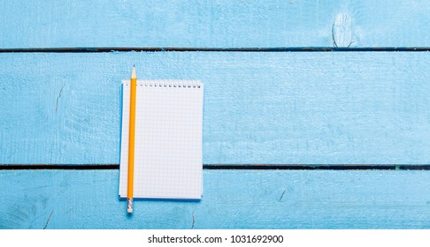 Pencil and notebook on blue background