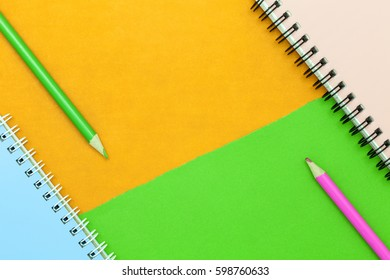 pencil and notebook on colorful paper background.