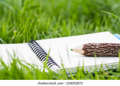 Pencil and notebook on grass