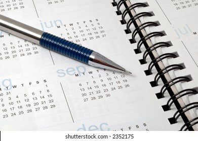 A pencil on calender of a notebook.