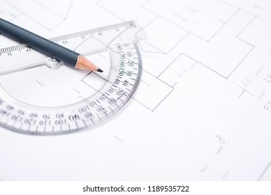Pencil on a transparent protractor on the table in the draftsman. Architectural prints and print rolls and a drawing instruments on the worktable. Background ready for your design