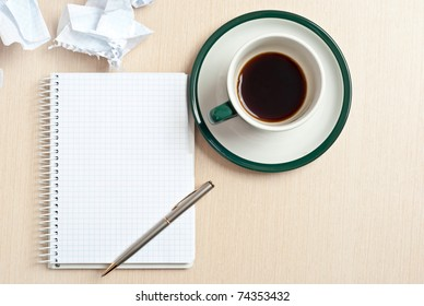 Pencil on a white notepad with cup of coffee on desk