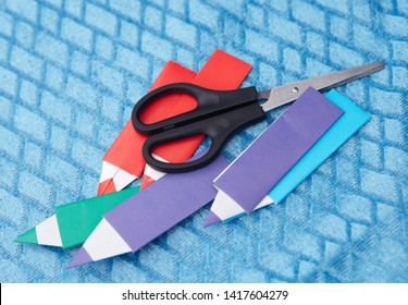 Pencil of origami color paper on a blue background. Children's creativity. Art of paper