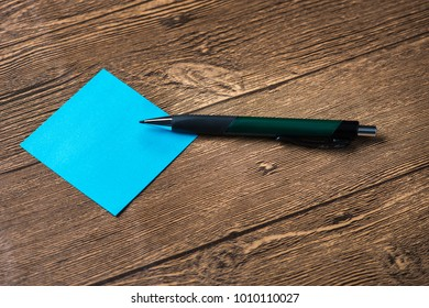 Pencil placed on post-it in wooden background