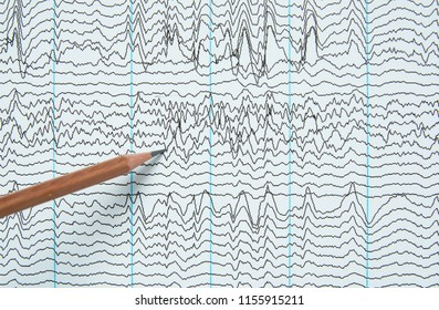 Pencil pointing at brain waves from electroencephalography or EEG in human