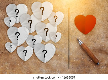 pencil with red heart and white paper with question mark inside love concept on brown texture background.jpg
