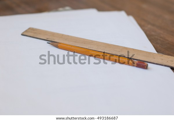 Pencil, ruler and paper on the table.